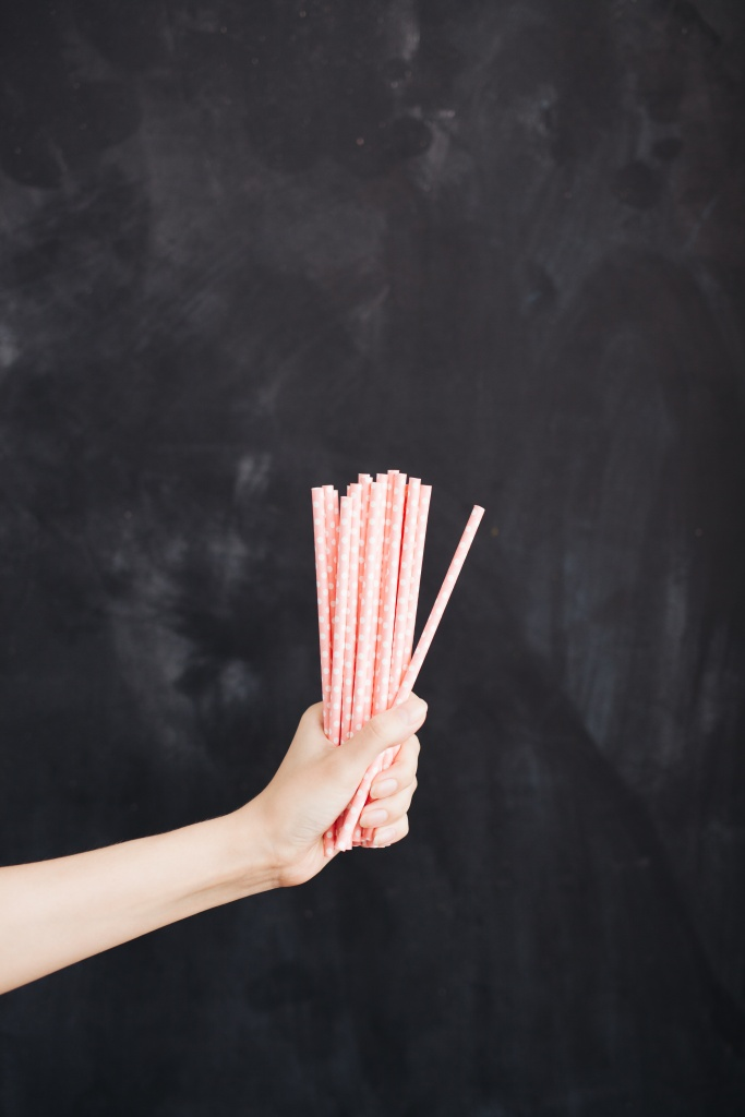 Woman hand hold cocktail straw on black background