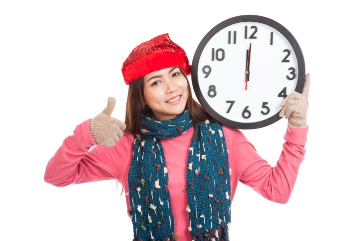 Asian girl t show thumbs up with red christmas ha and clock at m