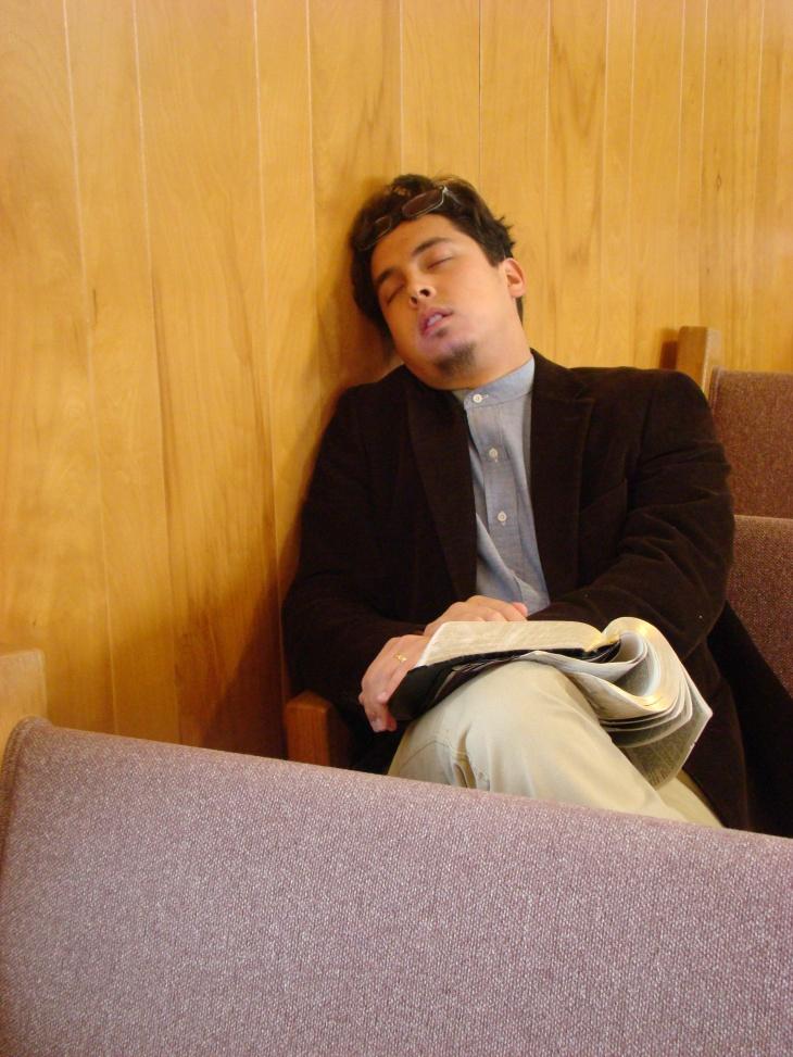Man sitting up sleeping in church